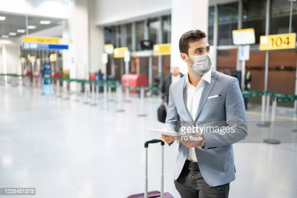 businessman holding digital tablet at airport using protective mask - travel ban stock pictures, royalty-free photos & images