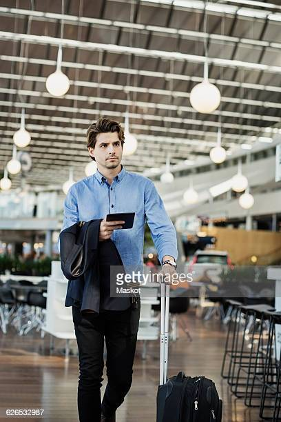 Businessman holding digital tablet while walking at airport
