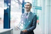Businessman holding digital tablet with glowing lights coming out of it