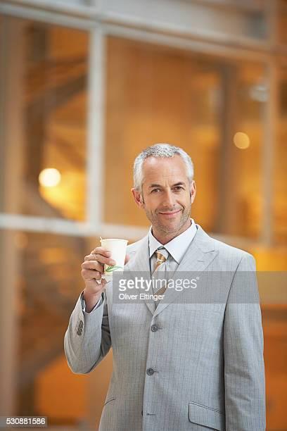 businessman holding disposable cup - oliver eltinger stock-fotos und bilder