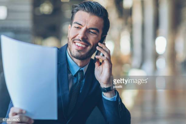 Businessman holding documents and talking on the phone