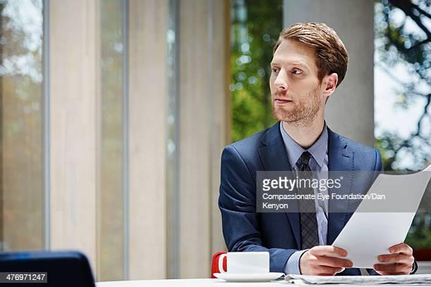 Businessman holding documents at desk