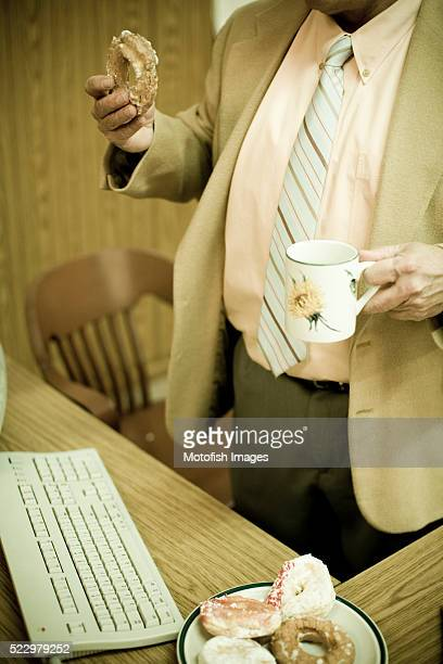 Businessman Holding Donut and Coffee Mug