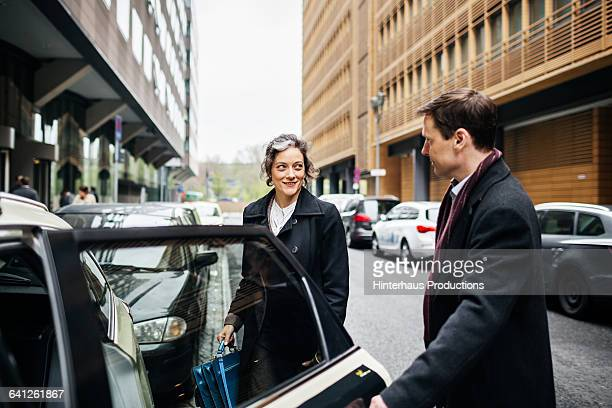Businessman Holding Door of a taxi for Woman