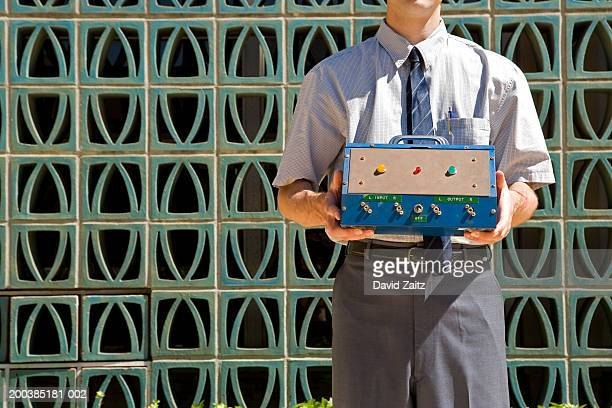 businessman holding electronic device in front of wall, mid section - inventor stock pictures, royalty-free photos & images
