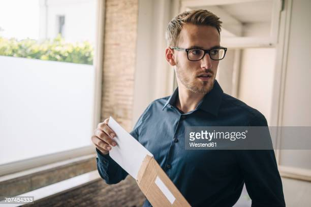 Businessman holding envelope turning around