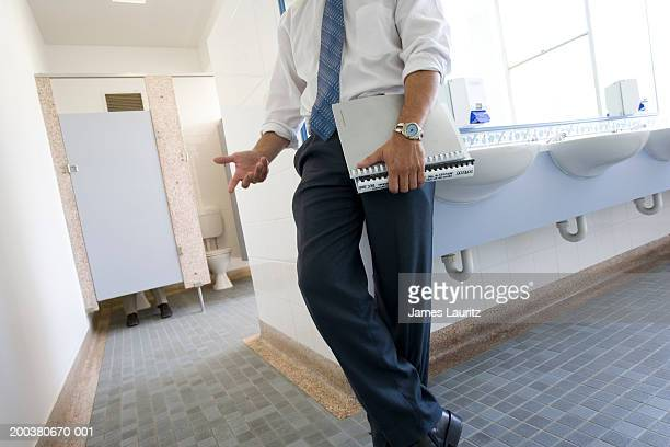Businessman holding file leaning against sink in office toilets