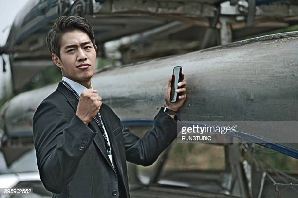 Businessman holding fist with cell phone