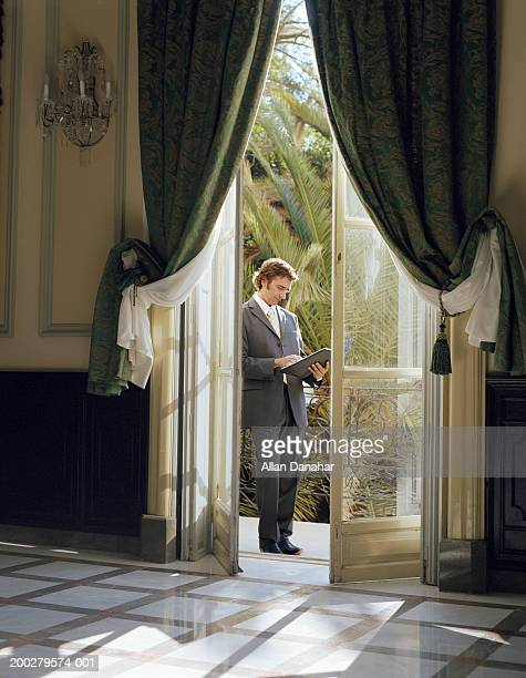 Businessman holding folder, standing on balcony, view through doorway
