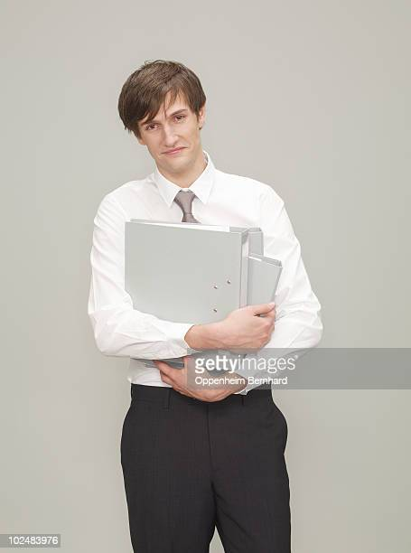businessman holding folders in his arms