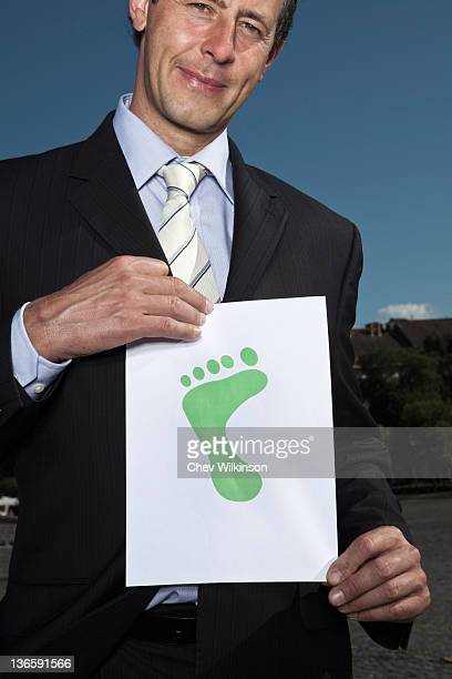 businessman holding footprint on paper - carbon footprint stock pictures, royalty-free photos & images