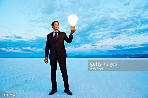 Businessman holding giant lightbulb in desert.