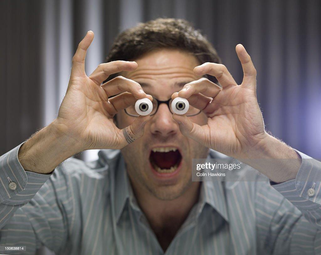 Businessman holding glass eyes : Stock Photo
