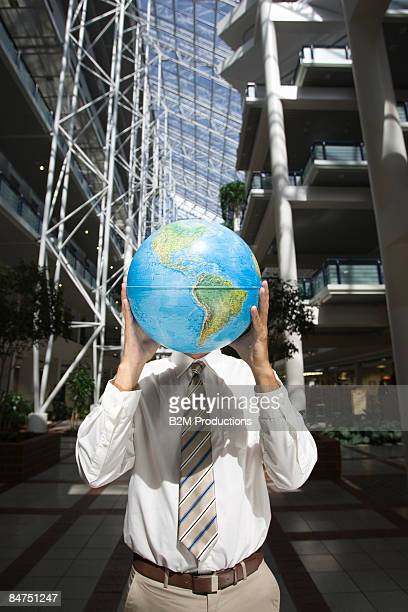 Businessman holding glowing globe in front of fac
