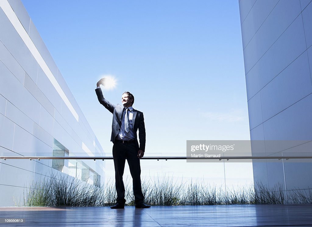 Businessman holding glowing light on balcony : Stock Photo