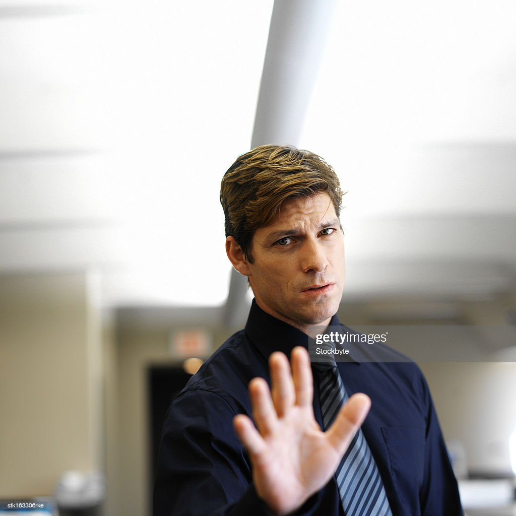 businessman holding hand up in front of camera close-up : Stock Photo