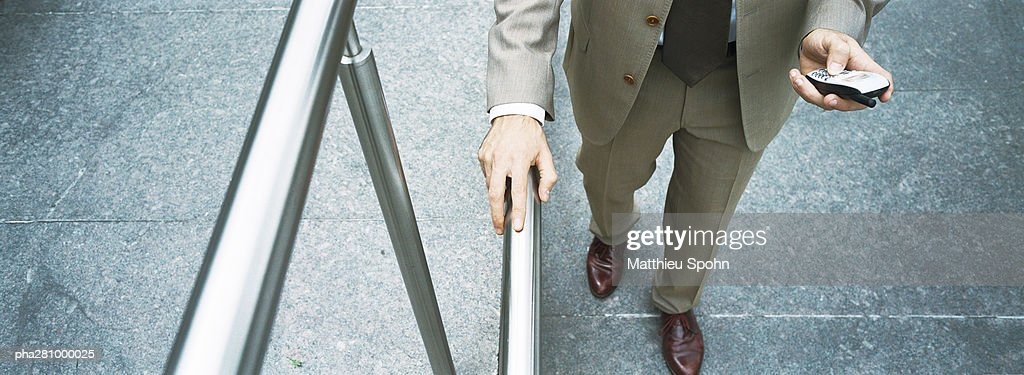 Businessman holding handrail and dialing cell phone, waist down, high angle view, panoramic : Stockfoto