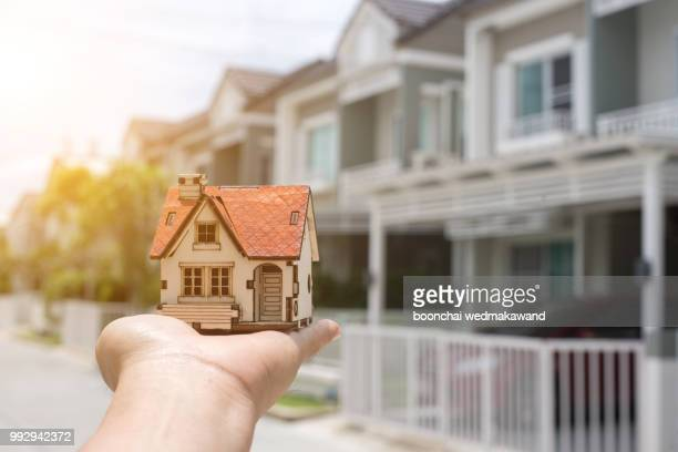 businessman holding home model. loan concept - home insurance stock pictures, royalty-free photos & images
