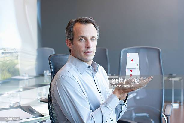 Businessman holding house of cards in conference room