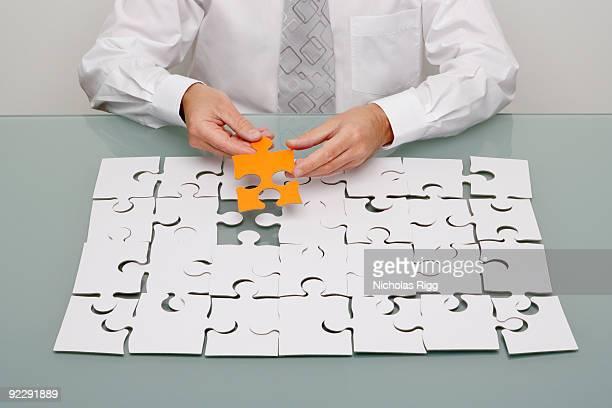 Businessman holding jigsaw piece.