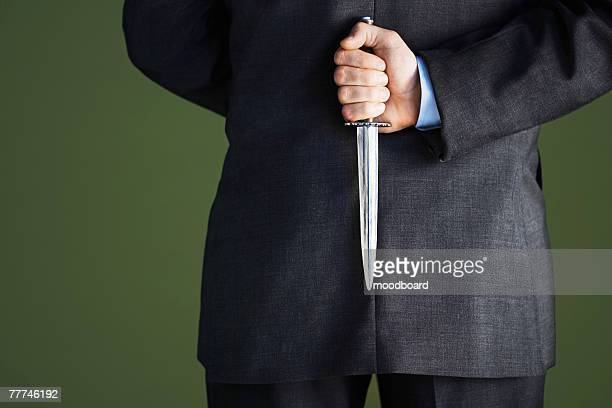 businessman holding knife behind back - samenzwering stockfoto's en -beelden