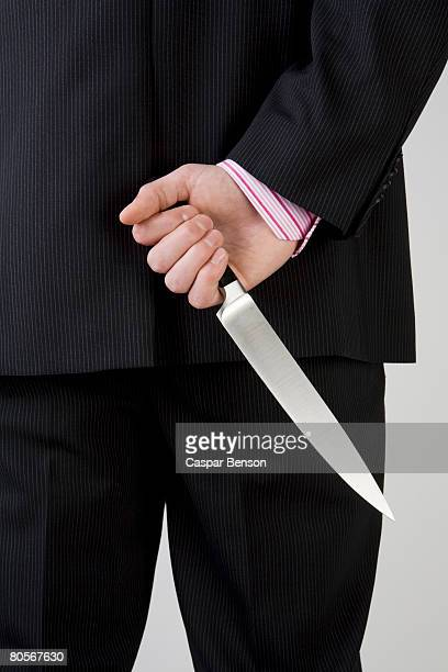 A businessman holding knife behind his back