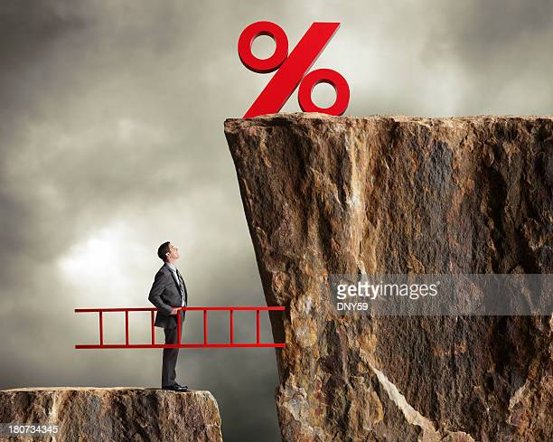 businessman holding ladder staring up at higher interest rates - interest rate stock pictures, royalty-free photos & images