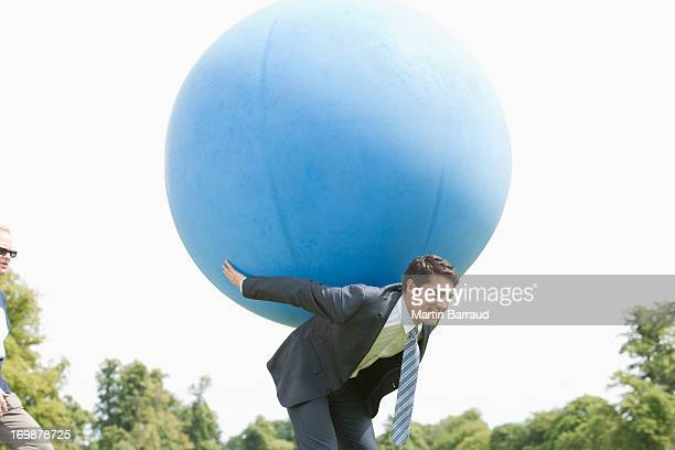 businessman holding large ball on back - man with big balls stock photos and pictures