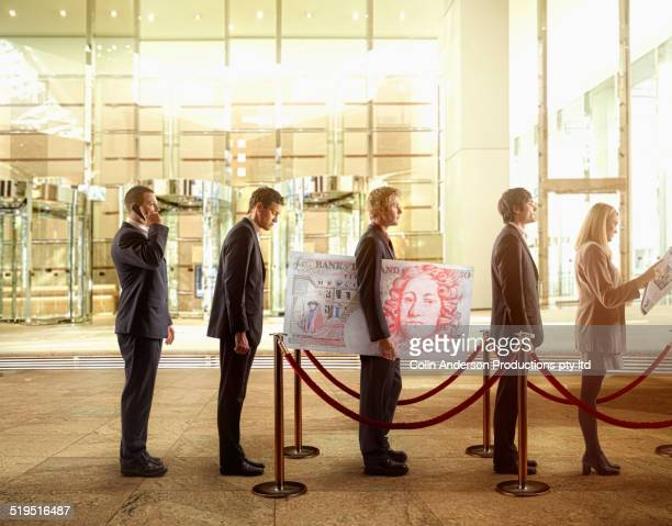 Businessman holding large British pound in bank line