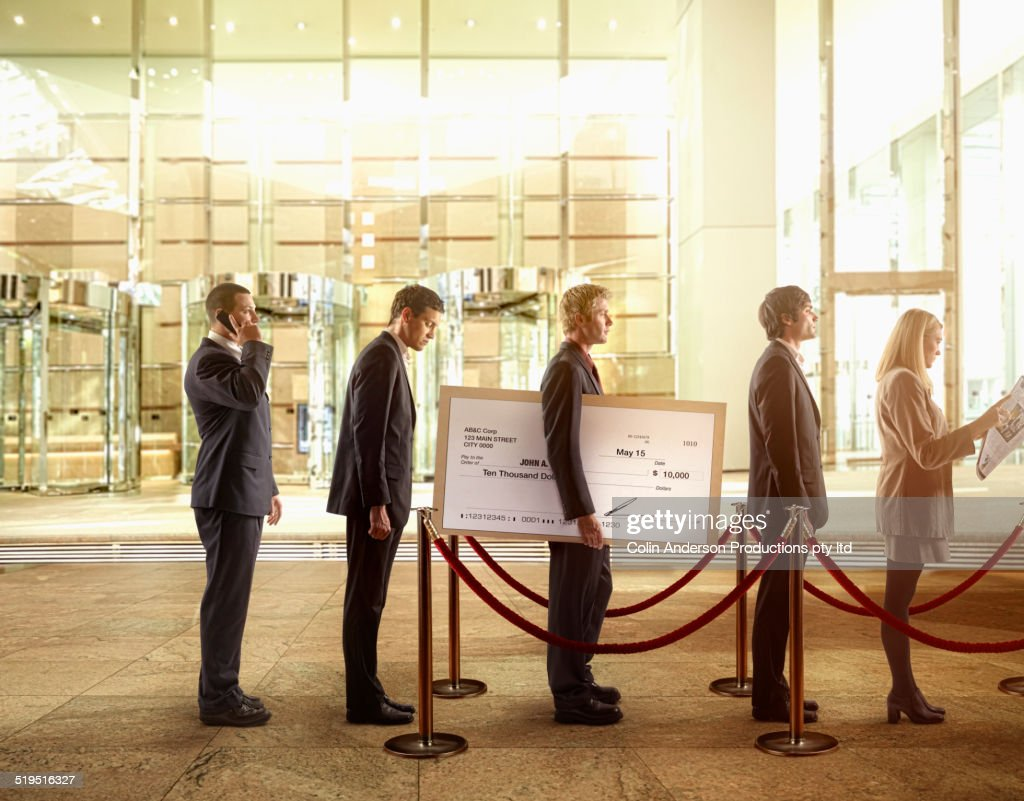 Businessman holding large check in bank line : Stock Photo