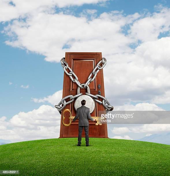 Businessman holding large key looking up at padlocked door