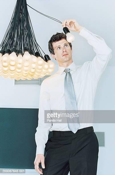 Businessman holding lightbulb away from bunch of hanging lightbulbs