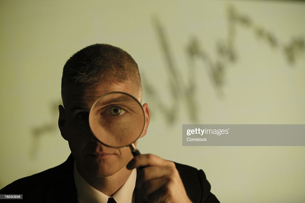 Businessman holding magnifying glass : Stock Photo