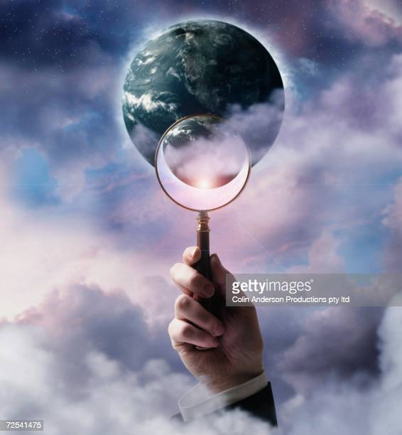 Businessman holding magnifying glass up to planet Earth