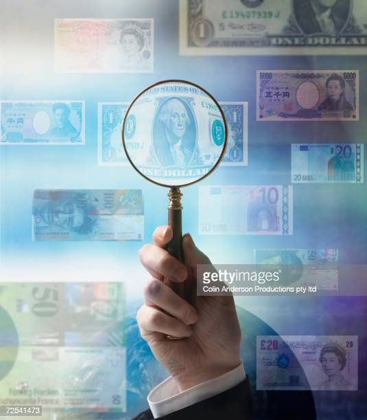 Businessman holding magnifying glass up to world currencies