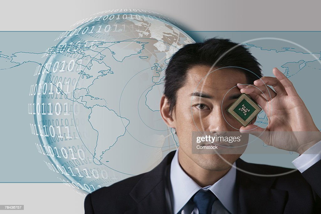 Businessman holding microchip with globe and binary code behind him : Stockfoto