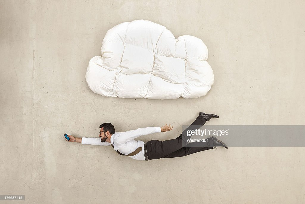 Businessman holding mobile phone and flying below cloud shape pillow : Stock Photo