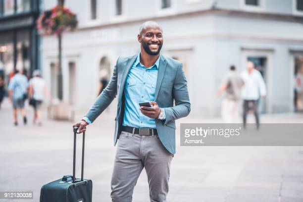 businessman holding mobile phone and standing on city street - business travel stock pictures, royalty-free photos & images
