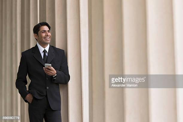 Businessman holding mobile phone, hand in pocket, smiling