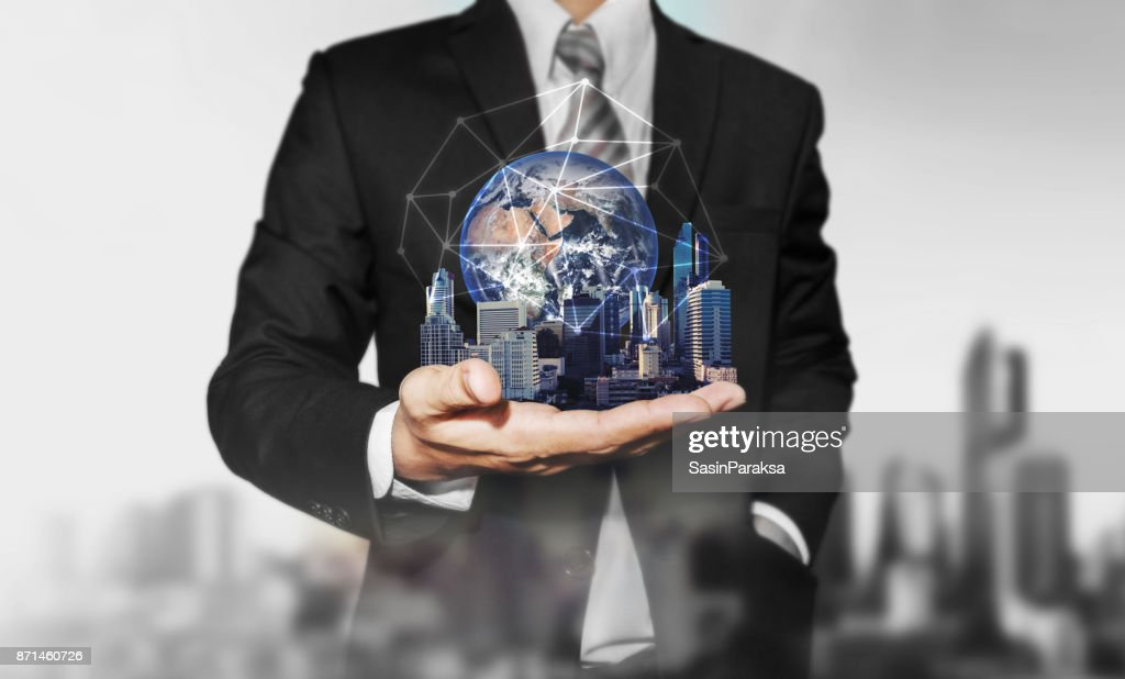 Businessman holding modern buildings with global network connection. Elements of this image are furnished by NASA : Foto de stock