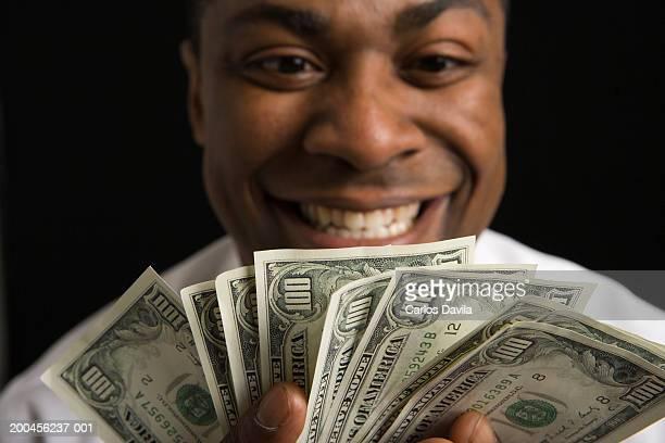 Businessman holding money, smiling, close-up