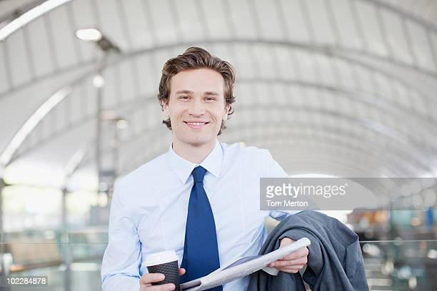 Businessman holding newspaper and coffee
