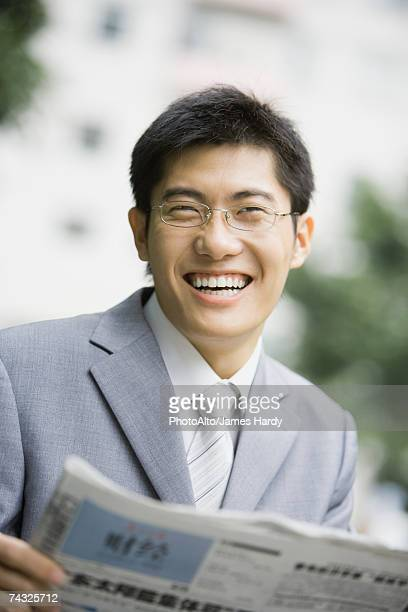 Businessman holding newspaper, laughing