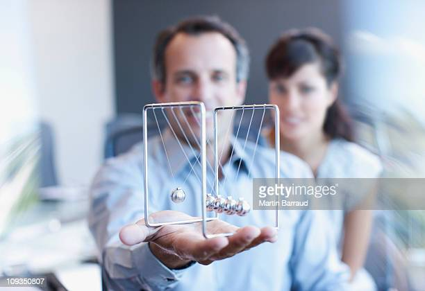 Businessman holding newtons cradle in office
