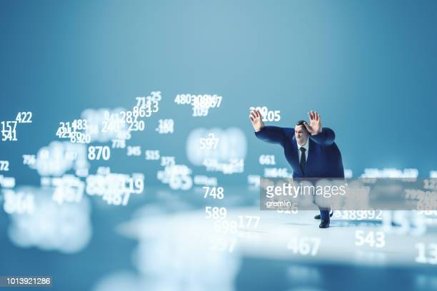 businessman holding off financial figures flying at him - numero foto e immagini stock