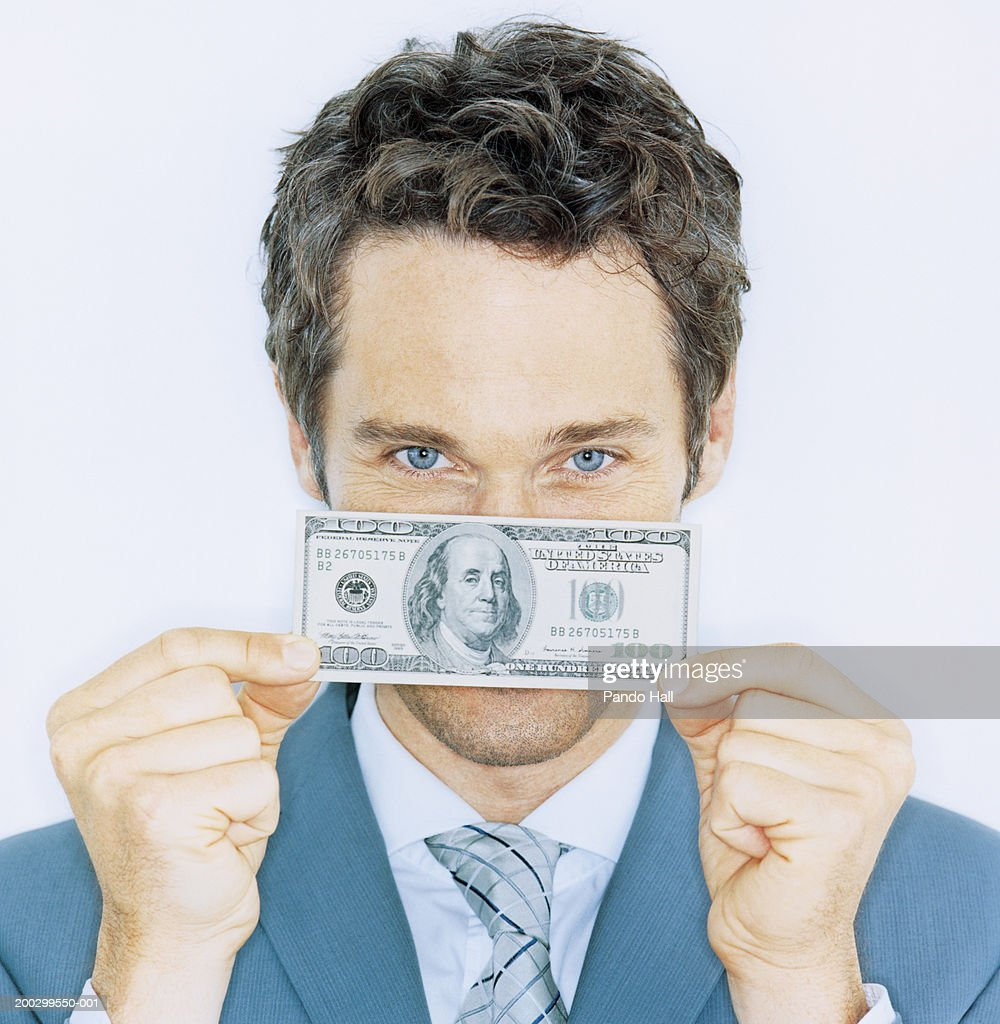 Businessman holding one hundred dollar banknote, portrait, close-up : Stock Photo