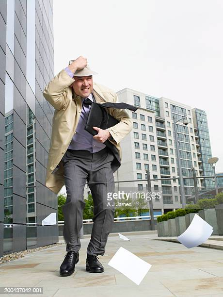 Businessman holding onto hat walking in wind, papers blowing on ground