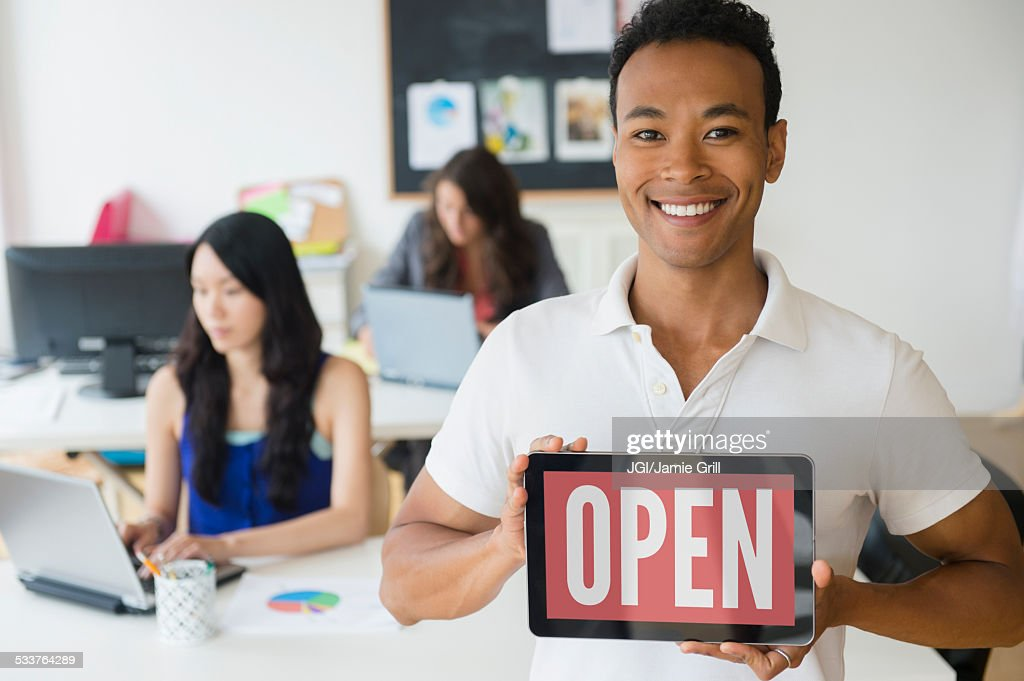 Businessman holding open sign on digital tablet in office : Foto stock