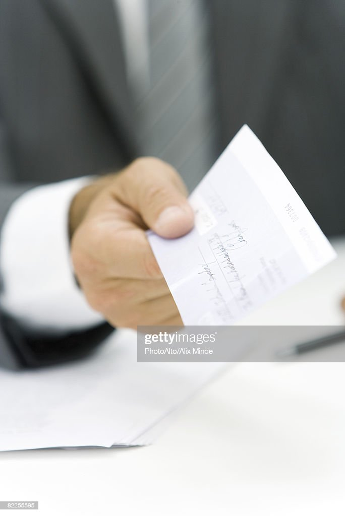 Businessman holding out check, cropped view of hand : Stock Photo