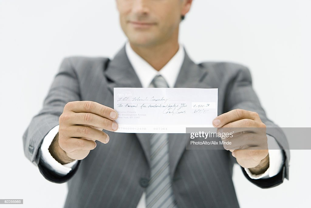 Businessman holding out check, cropped view : Stock Photo